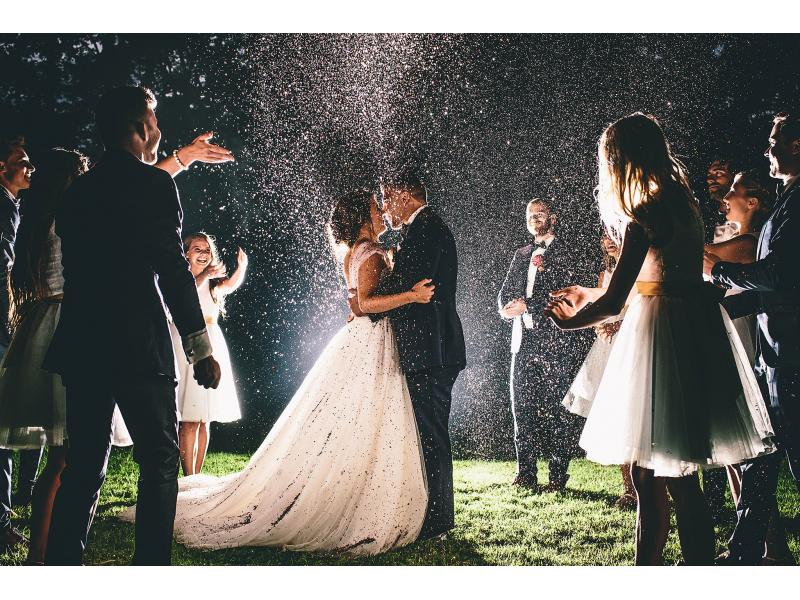 a bridal couple kissing as guests throw confetti at night