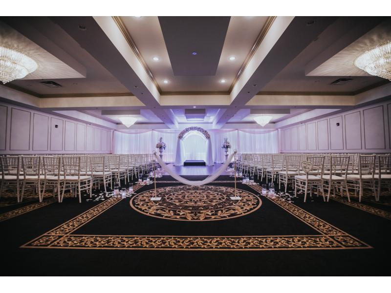 large hall setup for a ceremony with a decorated archway