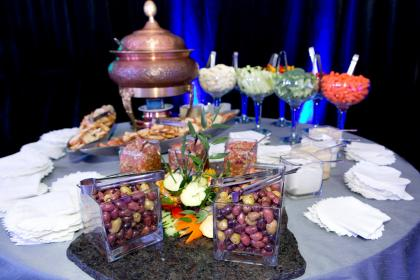 a table filled with stationary hors d'oeuvres like olives, vegetables and pitas