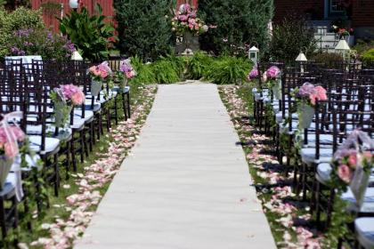 Aisle with white carpet, pink petals and mahogany chairs along either sides.